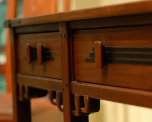 A detail of the Blacker table showing brackets and wood drawer pull.